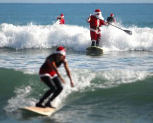 Approximately 150 Surfing Santas, elves, snowmen and other Christmas characters showed up at George Trosset's Surfing Santa event Christmas in the Sand in Cocoa Beach, Fla., Monday, Dec. 24, 2012. The event raised money for Grind for Life, which helps people with cancer. The ocean was filled with Surfing Santas:, men, women, boys and girls. (AP Photo/Florida Today, Malcolm Denemark)
